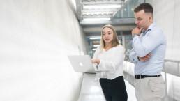 young professional overlegt met een andere young professional en kijken naar een laptop