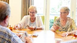 Oudere vrouwen en mannen aan het kaarten