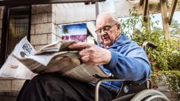 oude man in rolstoel leest een krant