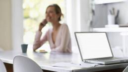 Vrouw belt na drijfveren onderzoek met een laptop op tafel